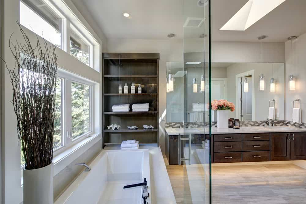 A large primary bathroom with hardwood floor and built-in shelving.