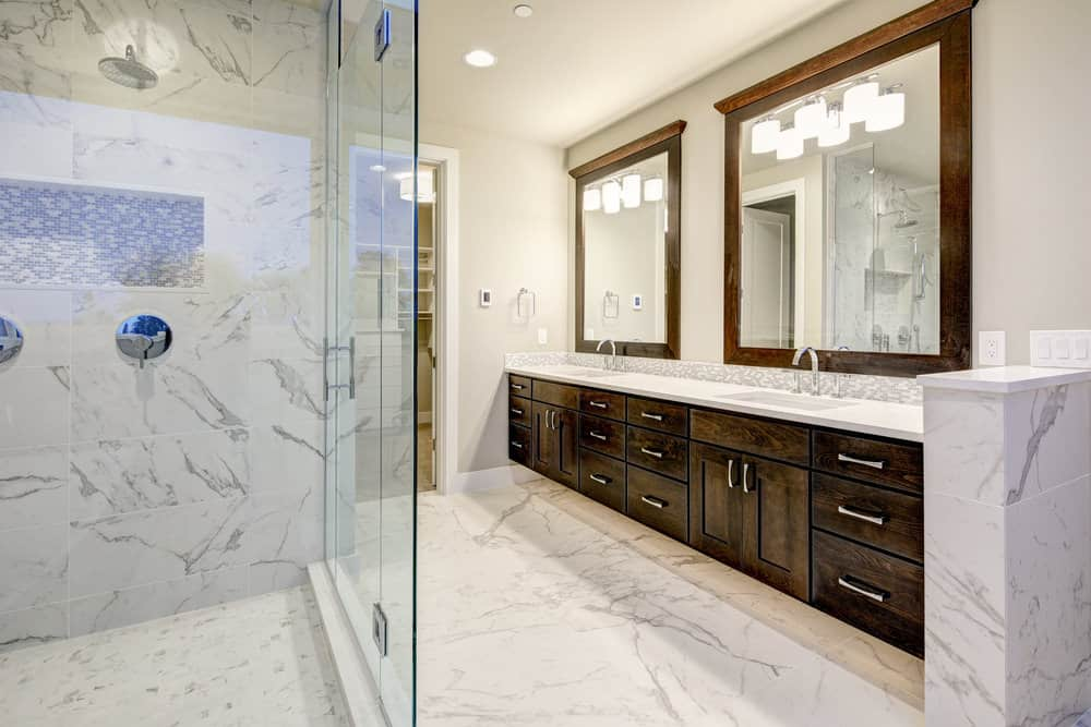Large primary bathroom with marble flooring and shower room walls. The long counter with two sinks features smooth white countertop.
