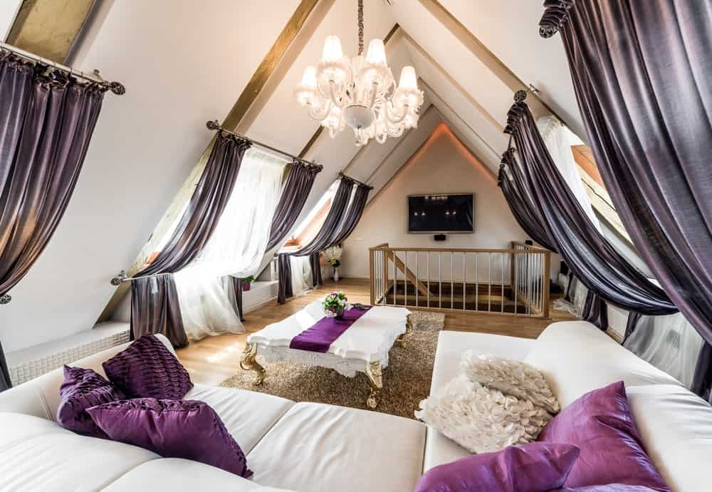 An attic living room illuminated by a white chandelier that hung over the classy coffee table lined with a purple runner. It has black drapes and white sectional dilled with fluffy pillows.