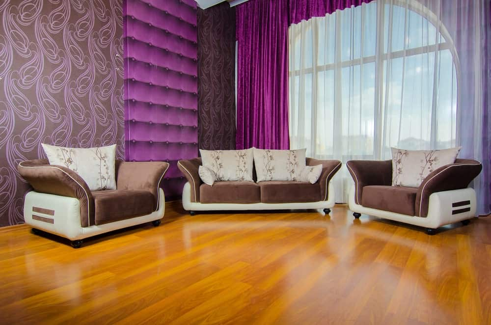 Purple living room with wallpaper, tufted wall, flowy curtains and modern brown seats over rich hardwood flooring.