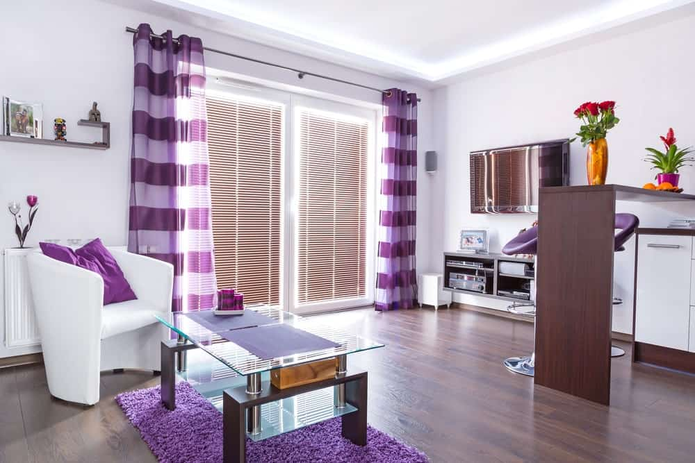 A sleek white armchair faces the glass top coffee table that sits on a purple area rug. This room has hardwood flooring and full height windows covered in blinds and striped sheer curtains.