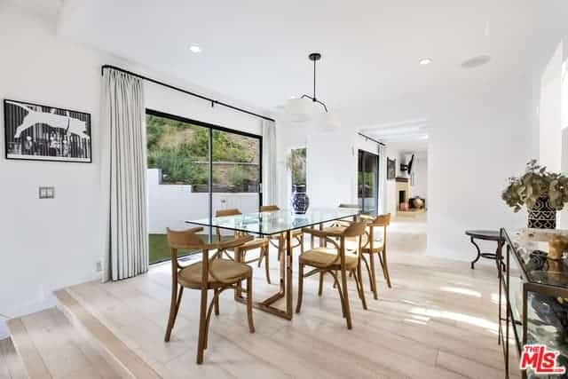 The wooden armchairs surrounding the glass-topped dining table stands out in this bright and airy Scandinavian-Style dining room. It has light-hued flooring, white walls and a white ceiling that is brightened up by the massive sliding glass tables.