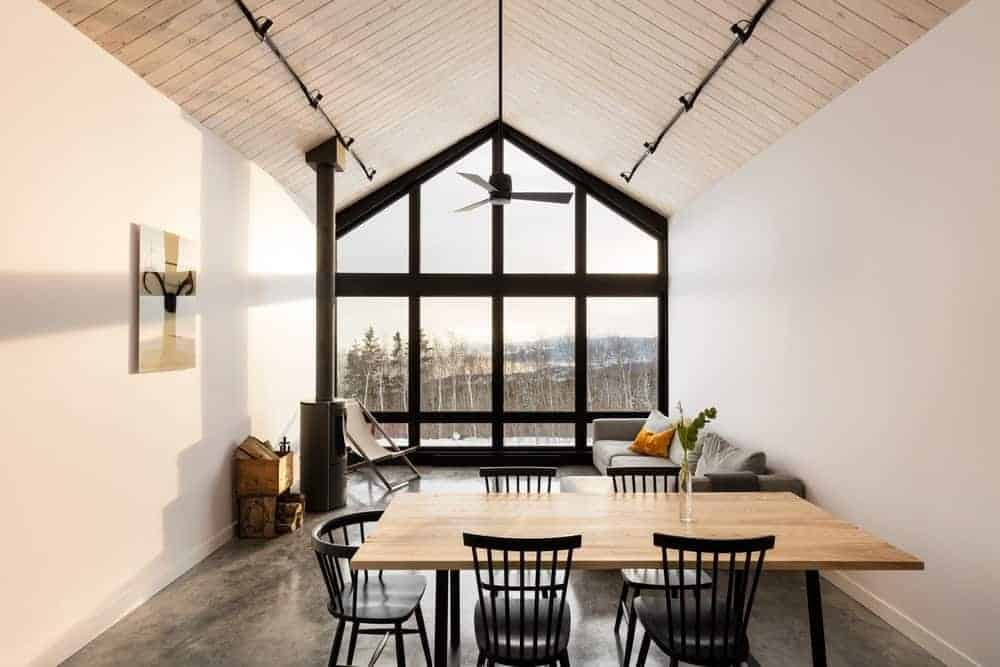 This dining area is part of a great room that houses the living the room as well. The simple wooden dining table is surrounded by black wooden slat-backed chairs that mirror the dark outlines of the massive glass window that goes up to the high cathedral ceiling.