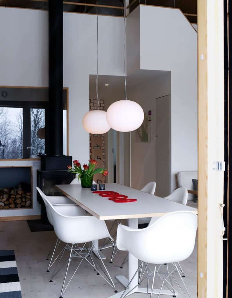 The modern plastic armchairs of this Scandinavian-Style dining room matches with the white rectangular dining table. This area has two spherical pendant lights hanging from a high ceiling. The warmth is provided by the dark iron fireplace by the head of the table.