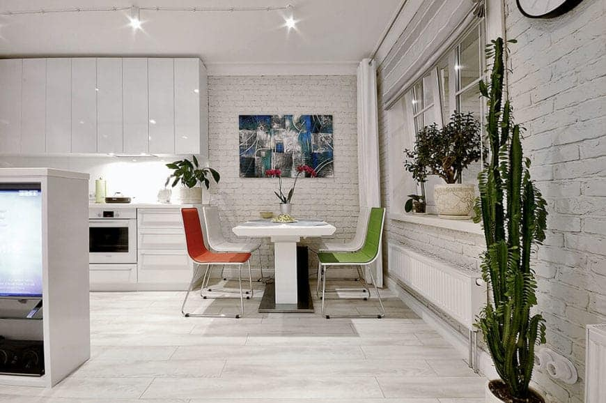 This dining area is fixed into a cove-like area beside the kitchen. It has textured white brick walls accented with a wall-mounted colorful painting looking over the modern white table. This table has colorful modern dining chairs illuminated by the pin lights on the white ceiling.