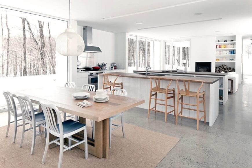 This bright and airy Scandinavian-Style dining room has a heavy wooden dining table paired with six slat-backed chairs that are brightened up by the snowy forest landscape outside the massive glass window dominating the wall at the head of the table.
