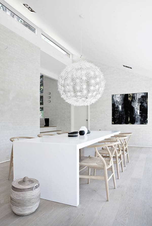 The bright and white dining room has subdued wooden elements that complement the white shed ceiling, walls, and modern sleek white table. The wooden wishbone chairs with woven wicker seats are paired with a woven wicker basket for a rustic accent.