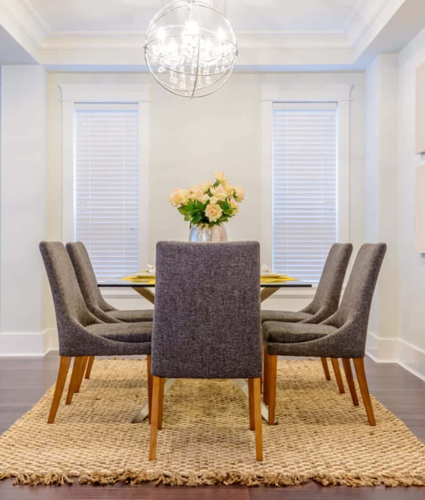 The white walls and white coffered ceiling are brightened up by the brilliant chandelier with a spherical design. This is contrasted by the dark gray cushioned dining chairs surrounding the glass-topped table. Over the hardwood flooring is a woven brown area rug.