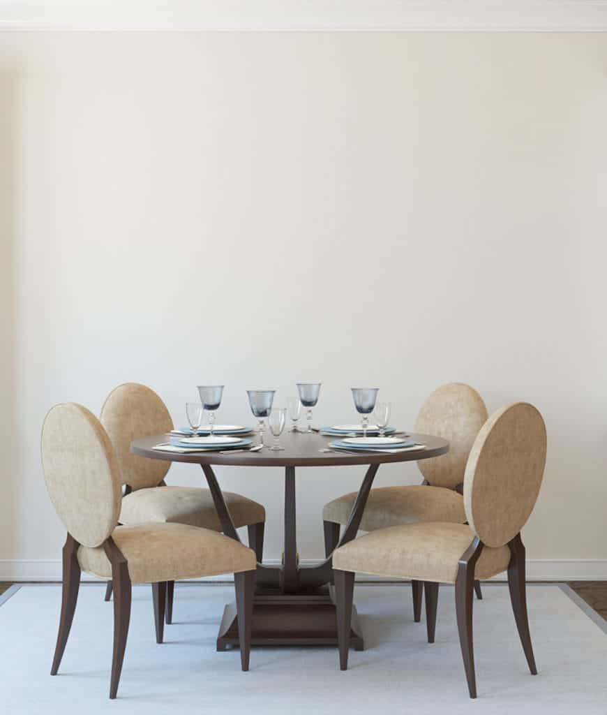 This is a simple Scandinavian-Style dining room with a circular wooden table that contrasts the white walls and white area rug beneath it. It is surrounded by four cushioned federal oval backed chairs with light brown hues to complement the dark wood.
