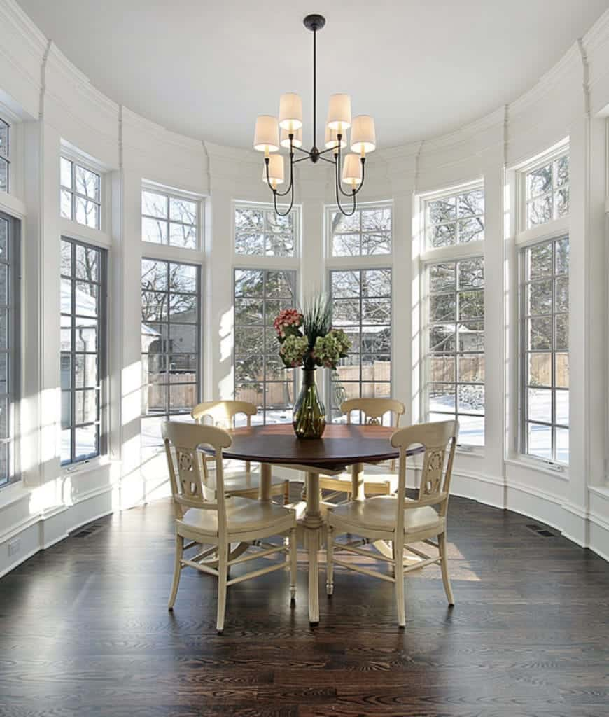 This is a circular and airy dining room that is surrounded by tall windows that complement the high white ceiling where a modern chandelier hangs. In the middle of the circular room is the traditional wooden table paired with matching white wooden chairs that stand out against the hardwood flooring.