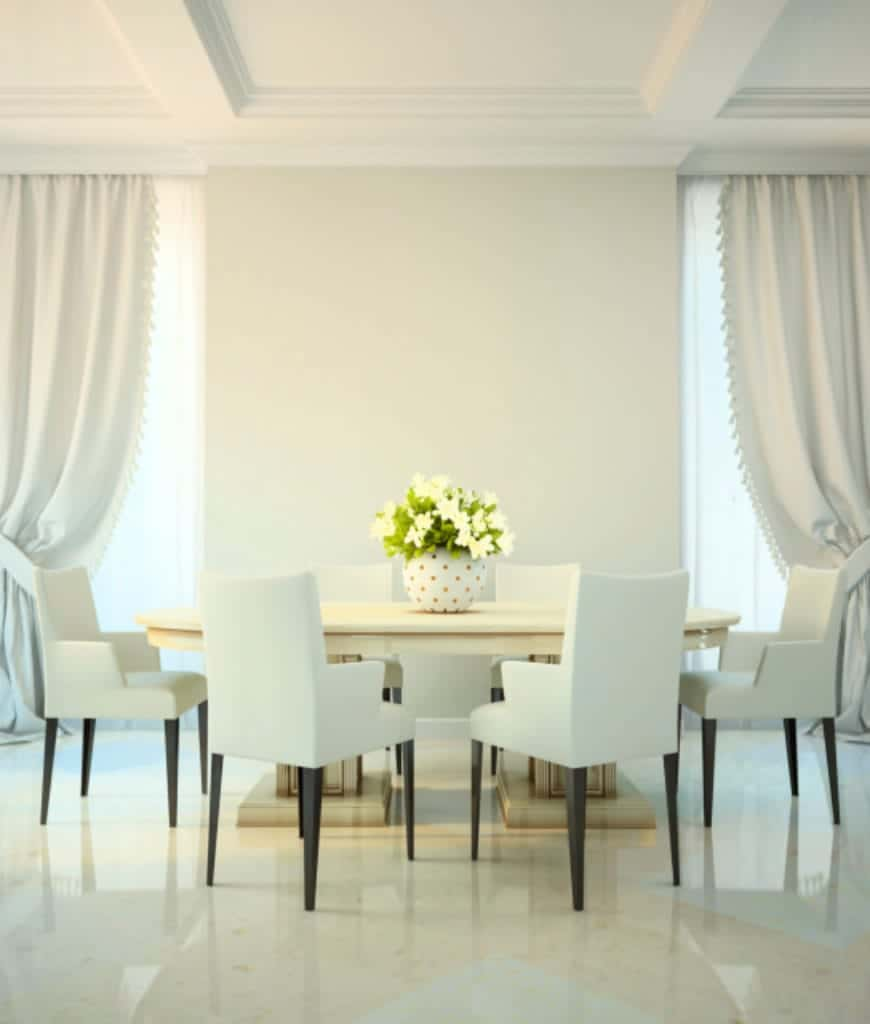 The oblong white dining table is flanked by two curtained tall windows that bring in an ethereal light over the Scandinavian-Style dining room. This is reflected by the sleek white marble flooring that contrasts the dark wooden legs of the white armchairs.