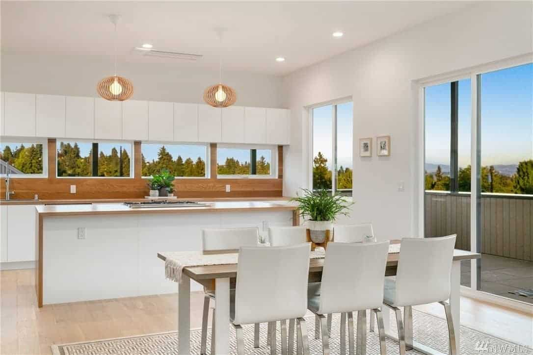 The hardwood flooring is covered by a patterned area rug that marks the dining area. There is a wood-topped dining table with metallic legs that match with the legs of the white modern chairs. These white dining chairs match well with the white ceiling and walls.