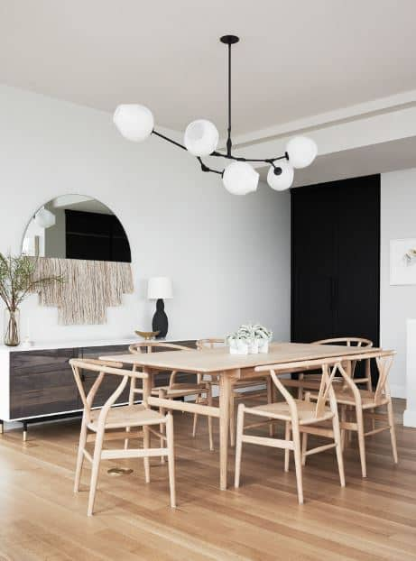 The wooden wishbone chairs perfectly match the rectangular wooden dining table that they surround as well as the hardwood flooring. These wooden elements stand out against the white walls and white ceiling that bears a modern black and white chandelier.