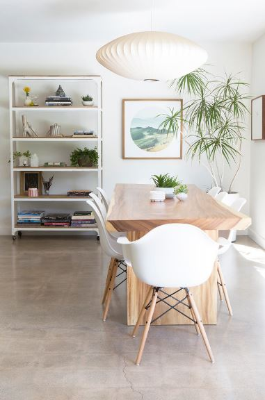 The peculiar white pendant light hanging over the wooden dining table matches well with the modern white dining chairs that have wooden legs. The white wall at the head of the table is adorned with shelves of decor and a wall-mounted painting beside a potted plant.