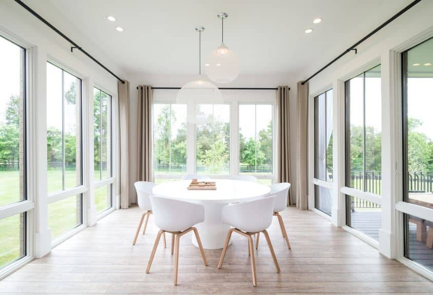 This Scandinavian-Style dining room maximizes the beauty of the surrounding nature with walls dominated by glass windows. One side has tinted glass to reflect the scenery presented by the other windows. This brightens up the white circular table and its matching white modern chairs.