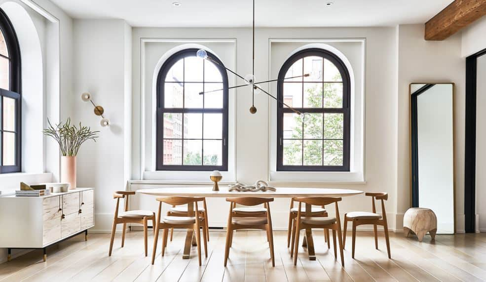 The long table of this Scandinavian-Style dining room is surrounded by simple wooden dining chairs over the hardwood flooring. This gives emphasis to the tall arched windows with navy blue frames against the white walls and white ceiling.