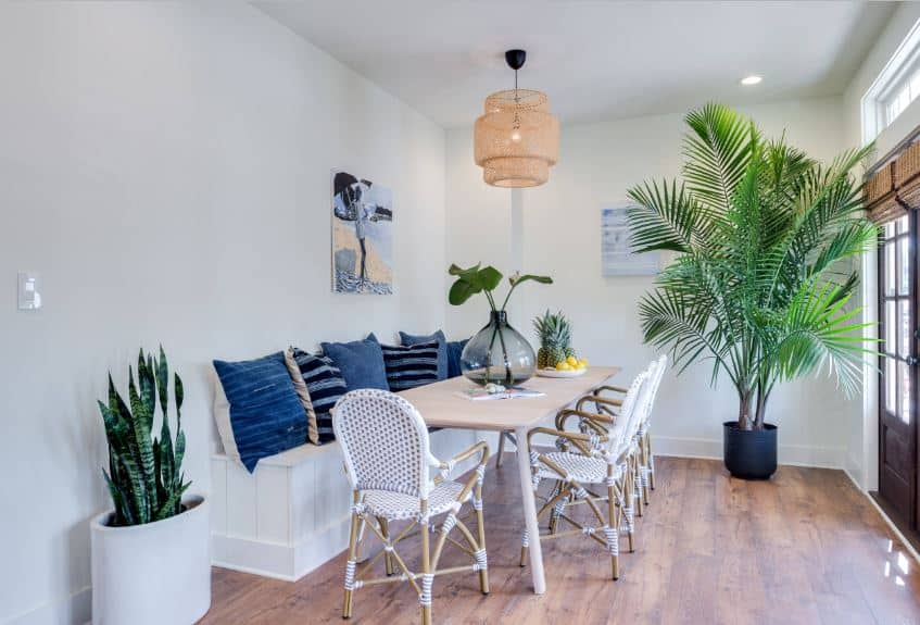 This dining area is against a charming nook of white walls that has a built-in white wooden bench with blue pillows. The wooden table is complemented by wooden armchairs that have white woven accents. This white dining area is augmented by a pair of potted plants that bring vibrancy.