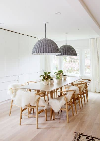 The stand-out elements of this Scandinavian-Style dining room are the dome-shaped gray pendant lights hanging over the rectangular wooden dining table. The wooden wishbone chairs surrounding it are given white fur cushions that match well with the white walls.