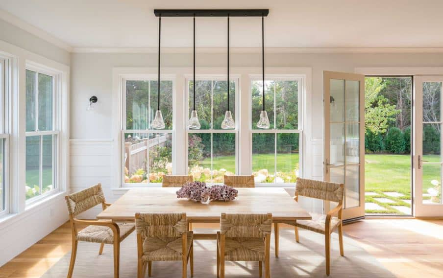 The woven wicker accents of the wooden dining chairs match the rustic scenery of the surrounding windows and French glass doors. The glass pendant lights over the wooden table is matched by the wall-mounted lamps on the white walls.