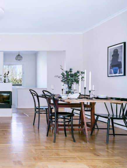 The elegance of this Scandinavaian-Style dining room is augmented by dark wood dining table and the surrounding black wooden chairs. They stand out against the hardwood flooring and white walls where a wall-mounted painting looks over the dining table.