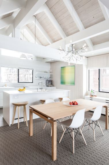 The patterned gray carpet of this Scandinavian-Style dining room stands out against the high white cathedral ceiling with exposed wooden beams. The wooden rectangular dining table stands out as well with its modern white dining chairs.