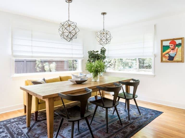 The bluish patterned area rug over the hardwood flooring is a nice touch to this dining room and its white walls and ceiling paired with a pair of wide windows. The wooden rectangular table is paired with a leather beige sofa on one side and black wooden chairs on the other.