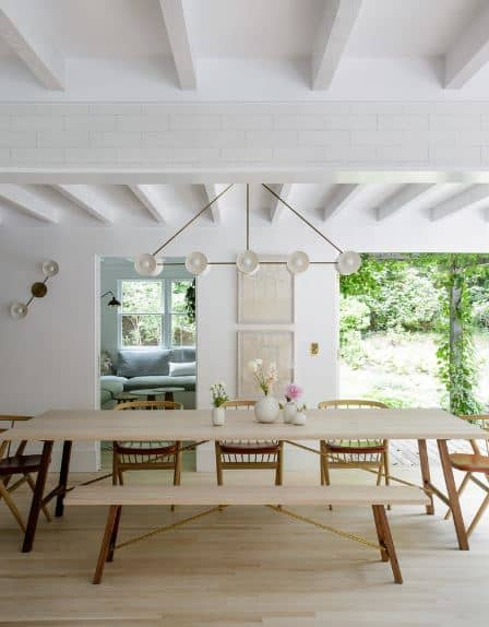 The white wooden ceiling has exposed beams that mold into the white walls that are accented with a wall-mounted lamp. This lamp has the same design as the modern chandelier hanging over the rectangular wooden table that is paired with a long wooden on one side and wooden chairs on the other.