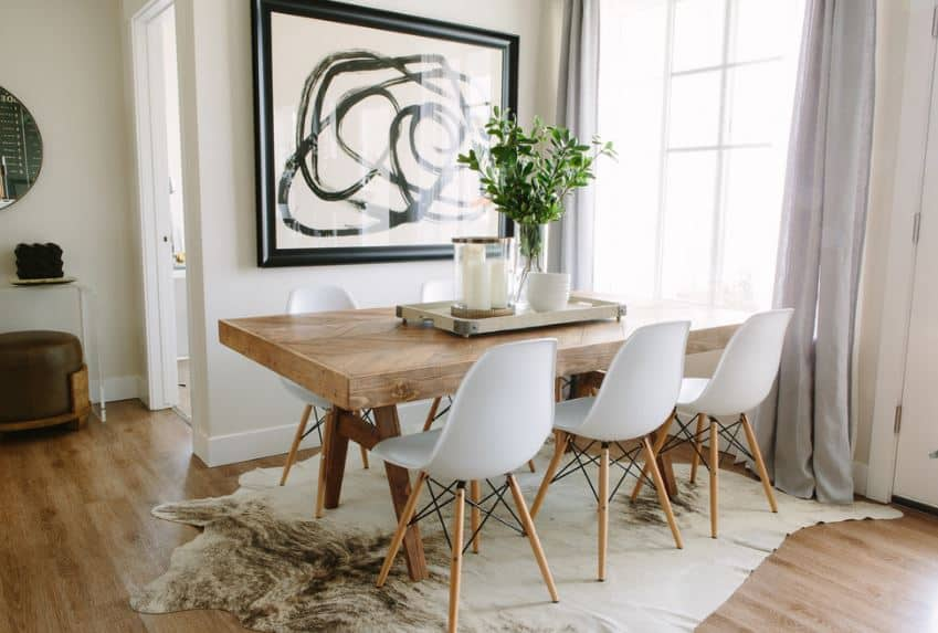 This dining area is placed into a charming corner with one side dominated by a curtained window while the other has a large framed painting mounted on it. The heavy wooden table is accented by an animal fur area rug beneath it.