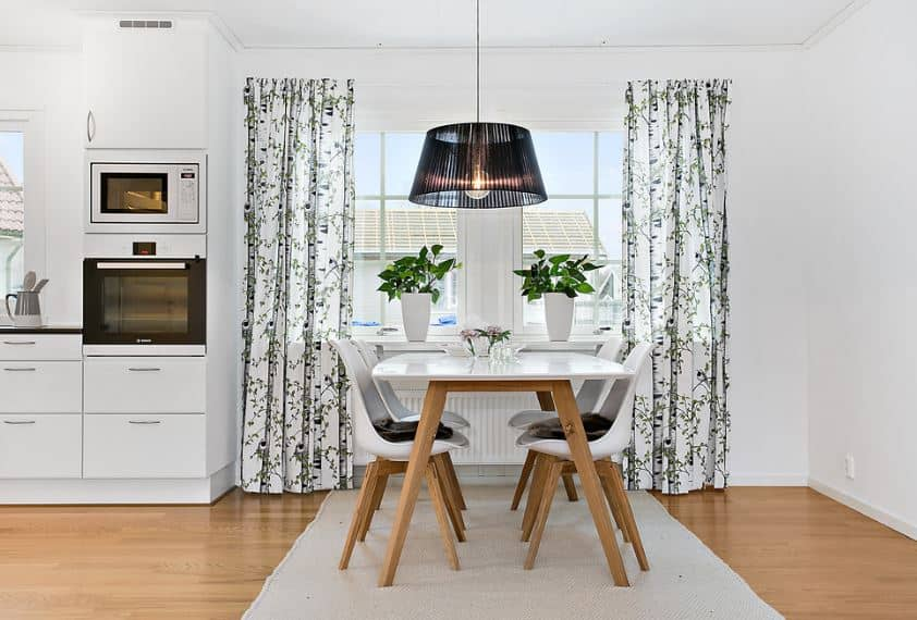 The head of the white wooden table is placed against the pair of windows that has leafy curtains accented with a pair of potted plants to emphasize the theme. In the middle of this symmetry hangs a modern pendant light that has a dark covering.