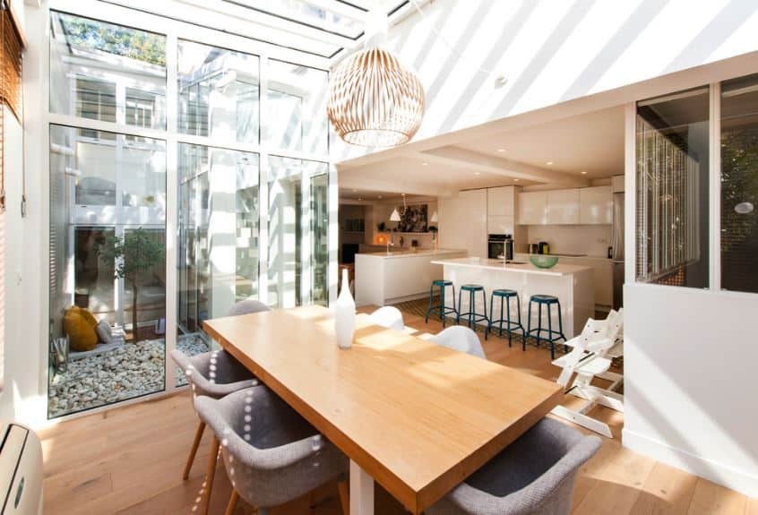 This charming Scandinavian-Style dining room puts emphasis on the surrounding natural light coming in from various glass windows as well as a glass ceiling that supports a modern pendant light with a patterned covering. The heavy wooden table is paired with gray cushioned armchairs.