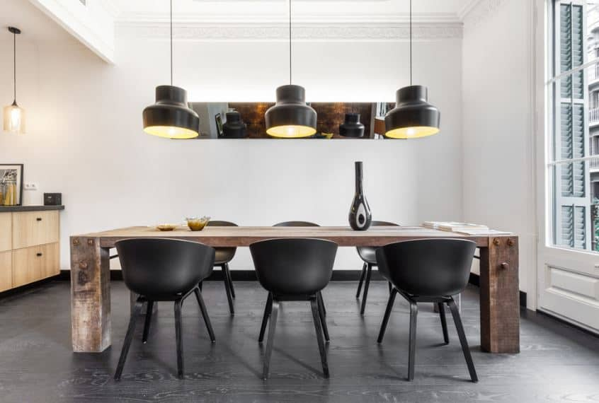 The dark and sleek modern pendant lights hanging the white ceiling is a perfect match for the black modern chairs and dark hardwood flooring. These dark and modern elements are contrasted by a rustic heavy wooden table with a large French window at its head.