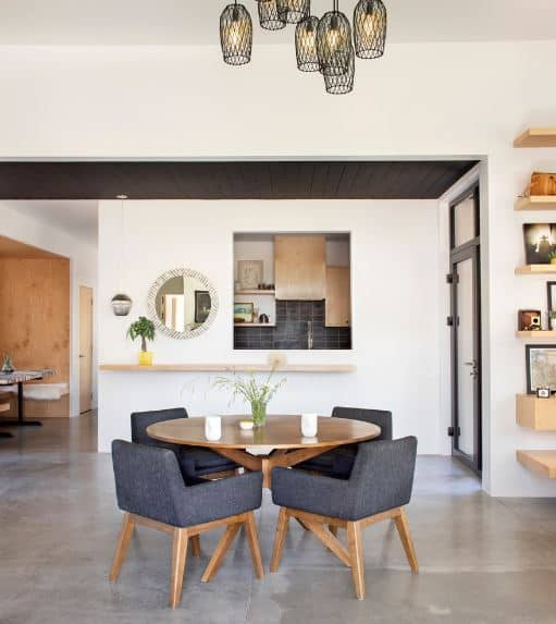 The gray cushioned armchairs have wooden legs that pairs well with the circular wooden dining table in this intimate Scandinavian-Style dining room. This is topped with a high white ceiling that has multiple pendant lights with dark covering.