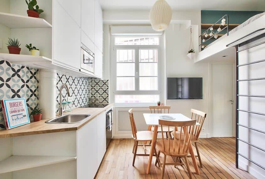 This Scandinavian-Style dining room maximizes the small hardwood floor space by sharing it with the kitchen peninsula on one side and on the other side is a ladder leading up to the bedroom. The wooden table is perfect for the small area and it is paired four slat-backed wooden chairs.