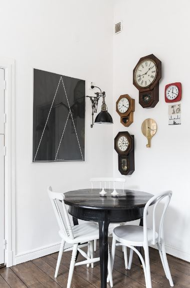This quaint corner of white walls is accented by a wall-mounted artwork on one side while the other is dominated by multiple wall clocks. This theme is a nice background of details for the plain dark wooden table and the white wooden chairs surround it.