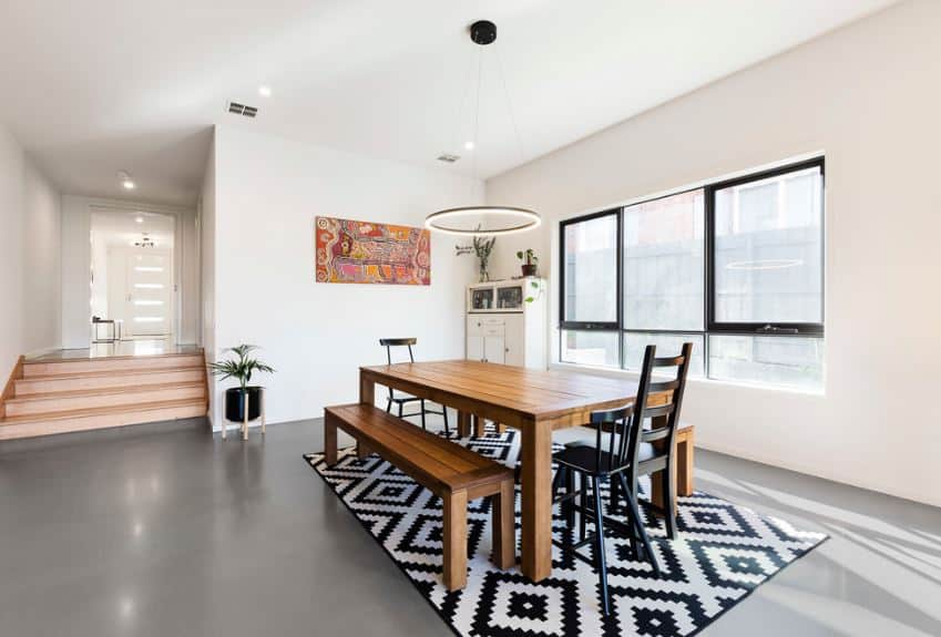 This dining area is marked with patterned black and white area rug over the sleek gray flooring. The wooden table is paired with matching wooden benches on either side and topped with a circular modern light hanging from the white ceiling.