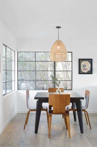 This Scandinavian-Style dining room is against a corner with a pair of wide windows that dominate that corner. The sleek black wooden dining table is contrasted by the modern wooden dining chairs surrounding it and added with a dash of rustic accent with a woven wicker pendant light.