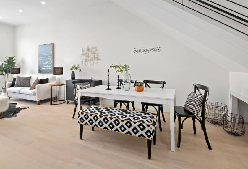 This dining area is situated right beneath the stairs forming a shed ceiling over the white modern table that is paired with a bench that has a black and white patterned cushion. The rest of the table is covered by wooden black chairs that stand out against the white walls.