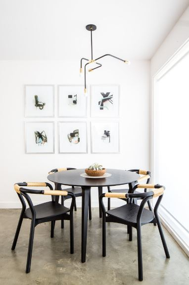 Beautiful black armchairs surround the black round dining table of this Scandinavian-Style ding room. These chairs match with the design of the modern dark iron chandelier hanging from the white ceiling as well as the artworks mounted on the wall.