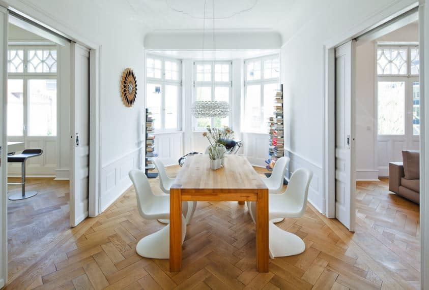 The area at the head of the wooden dining table is a charming round nook of windows flanked by bookshelves giving a nice view contrasting the white walls surrounding the Scandinavian-Style dining room with a patterned hardwood flooring.