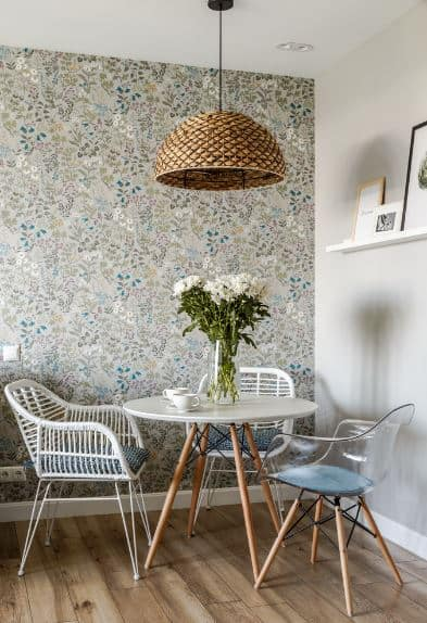 This is charming and chic dining corner with one wall covered in a wallpaper of colorful flowery patterns while the other is plain white with a single hanging shelf accented with framed artwork. These details are a nice background for the simple round wooden table and its armchairs.