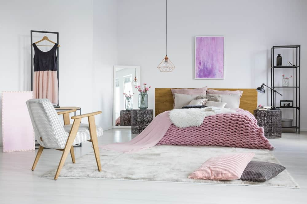 A Shabby Chic primary bedroom boasting a large bed setup with stylish bedside tables and a freestanding shelf.