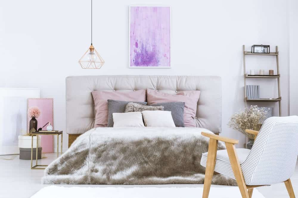A focused shot at this primary bedroom's luxurious-looking bed setup lighted by a pendant light. It has a freestanding shelf on the side and a small bedside table on the other.