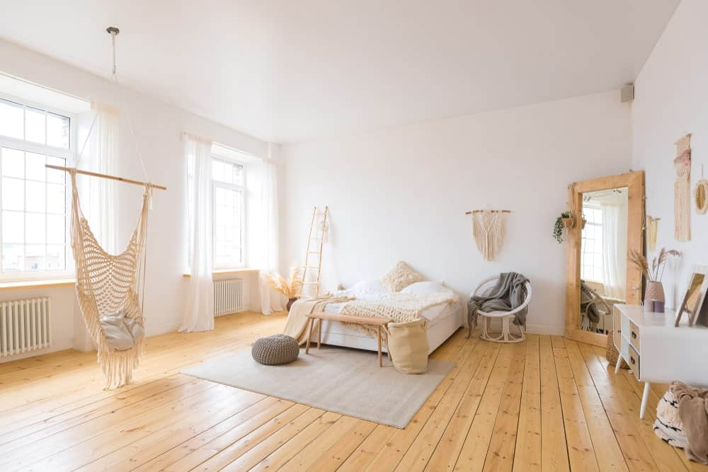 A spacious Shabby Chic master bedroom featuring white walls and white ceiling, along with hardwood flooring. The room offers a gorgeous bed setup and windows featuring lovely white window curtains.