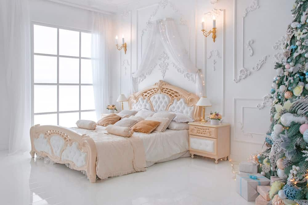 Shabby Chic primary bedroom featuring an elegant bed setup surrounded by classy white decorated walls lighted by wall lights. The room also has white hardwood flooring and windows with lovely white window curtains.