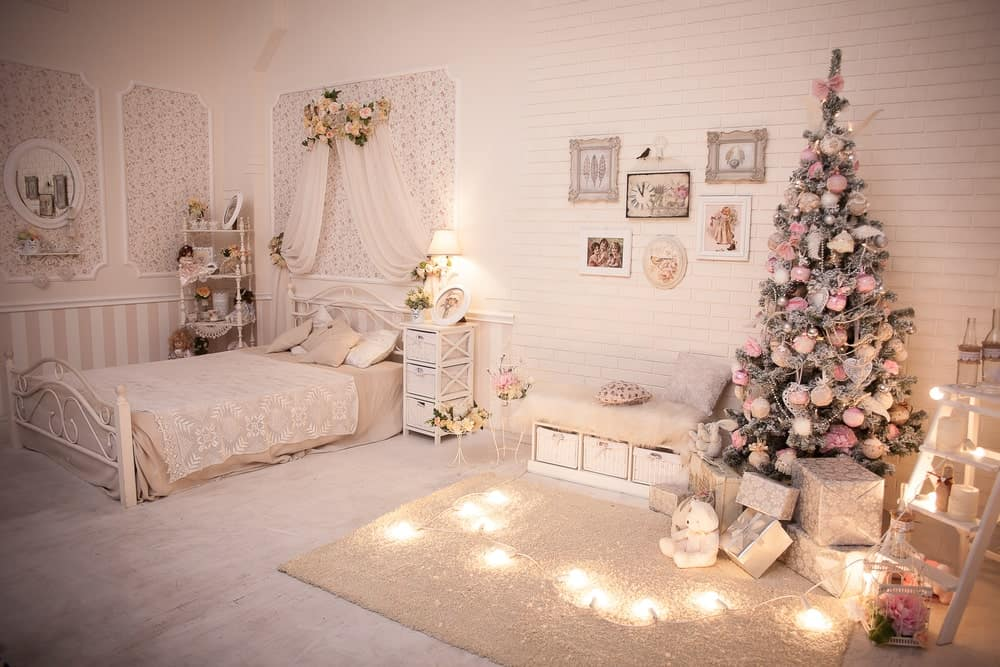A Shabby Chic primary bedroom with a lovely bed setup and classy wall decors, along with carpeted flooring. The room also boasts a gorgeous Christmas tree decoration on the side.