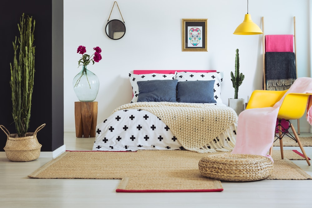 A focused look at this Eclectic primary bedroom's lovely bed setup lighted by a yellow pendant light matching the yellow sitting chair on the side.