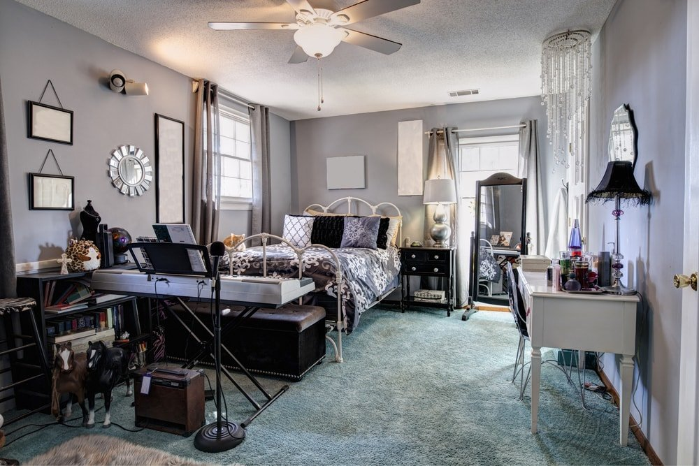 Large Eclectic master bedroom with carpet flooring and light gray walls. The room offers a classy bed and attractive wall decors.