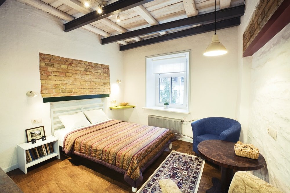 A small Eclectic-style bedroom featuring hardwood floors and a rustic ceiling with beams. The room offers a cozy bed and a pair of modern chairs on the side, along with a round coffee table.