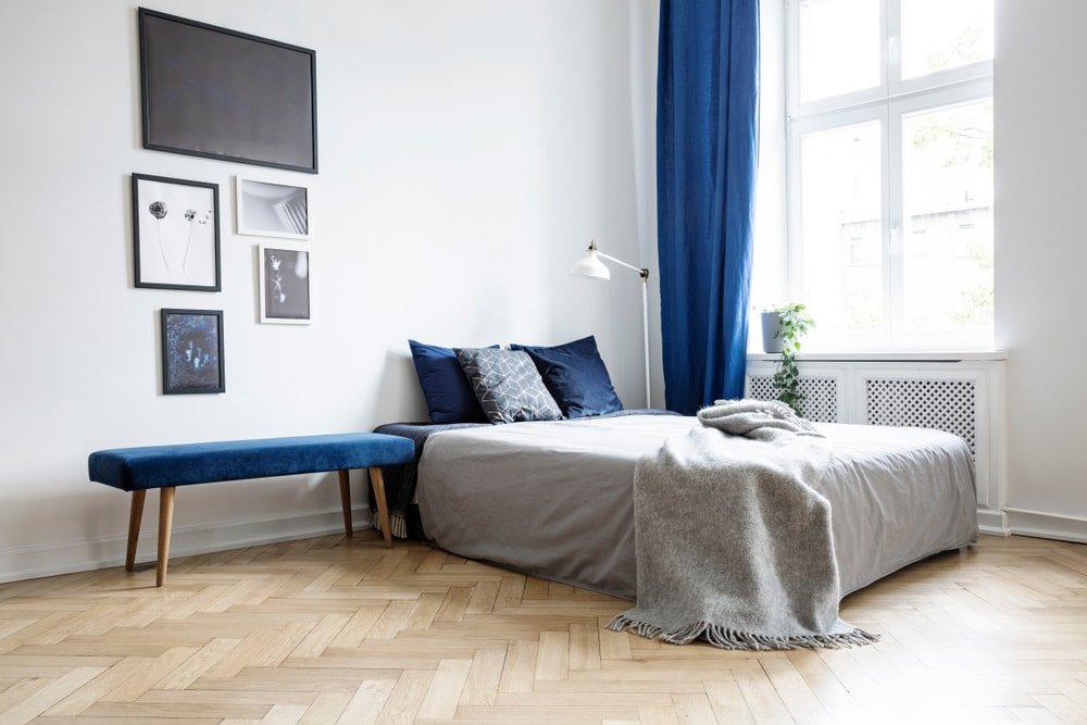 A spacious Eclectic master bedroom featuring white walls and herringbone-style hardwood floors. The room also features a blue accent color scheme.