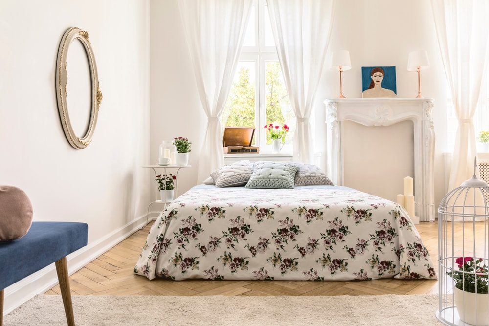A focused shot at this Eclectic primary bedroom's gorgeous bed set surrounded by white walls and lovely white window curtains.